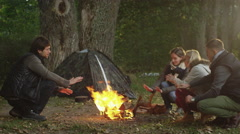 Group of people are sitting next to a campfire next to a tent in a forest - stock footage