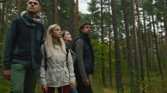 Group of people in autumn clothes are standing in a forest and looking around Stock Footage