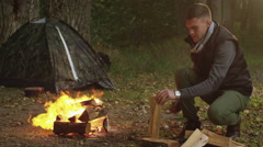 Man in autumn clothes is chopping wood with an axe and throwing it into the fire - stock footage