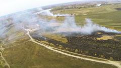 Stock Video Footage of Flight as  bird's eye's  with  swing  over  field with burning grass and smoke.