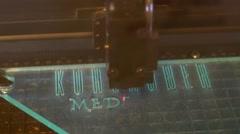 A lasercutter cutting a logo on plexiglas - stock footage