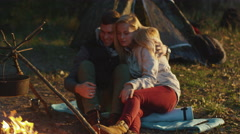 Young couple sit next to a campfire with boiling water and hug each other Stock Footage