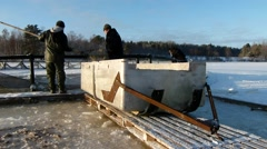 Guys picking up fishes from the cage to the sled. Stock Footage