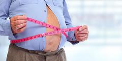 Obese man abdomen with measuring tape. - stock photo