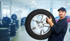 Car mechanic with a tire . - stock photo