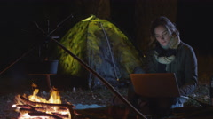 Young brunette woman is using a laptop next to a campfire at night Stock Footage