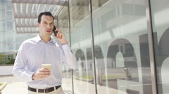 4K Attractive casual businessman talking on mobile phone outside office building - stock footage