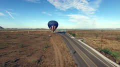 Aerial hot air balloon landing by busy road in desert Stock Footage