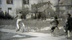 1938: Gang of kids rolling down the sidewalk together. Stock Footage