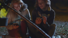 Two happy girls are sitting next to campfire at night and use their smartphones Stock Footage