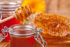 Fresh honey with dipper Stock Photos