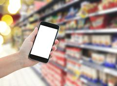 Hand holding a modern smartphone in supermarket Stock Photos