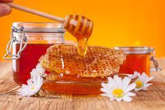Fresh honey with dipper - stock photo