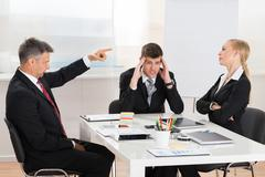 Mature Businessman Arguing With His Two Co-workers In Office Stock Photos