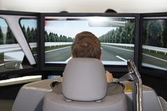 Male is trying a car simulator in a congress Stock Photos