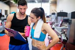 Trainer explaining workout regime to woman - stock photo