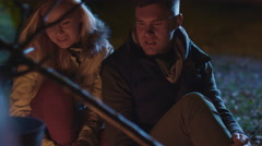 Young couple sit next to a campfire at night and hug each other Stock Footage