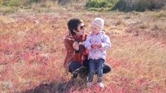Little kid girl with mother play outdoors on fresh air of countryside red nature - stock footage