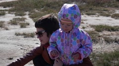 Mother and little kid daughter sit on shore and draw a wooden stick in the sand Stock Footage