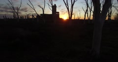 Aerial Drone scene of abandoned Slaughterhouse, sunset, dead trees in Epecuen Stock Footage