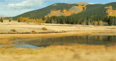 4K POV moving traveling by mountain hill with golden aspen pine trees and lake Stock Footage