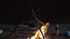 Motion shot of a campfire with a metal pot burning bright at night Stock Footage