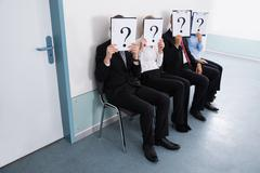 Businesspeople Sitting On Chair Hiding Behind Question Mark Sign Stock Photos