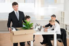 Unhappy Businessman Carrying Belongings In Box While Other People Working In  - stock photo