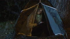 Young blond girl is using a tablet in a tent at night Stock Footage
