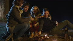Group of people are preparing meat on a campfire at night Stock Footage