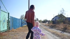Little kid girl with her mother walking in the nature of the countryside - stock footage
