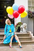 Colourful young woman with balloons sitting on a doorstep Stock Photos