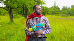 Stock Video Footage of Man in red mantle aiming and shooting with toy pistol on the field