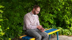 Smiling man in glasses sitting on a bench and surfing in touch pad Stock Footage