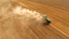 HD aerial footage of a modern tractor plowing dry fi - stock footage