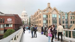 People walking on Millennium Bridge with St Pauls Cathedral on background - stock footage