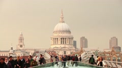 Stock Video Footage of View of St Pauls Cathedral in London with people walking on Millennium bridge