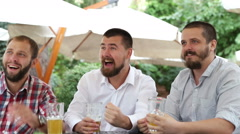 Men with beards in cafe outdoors watching match and looking very happy - stock footage