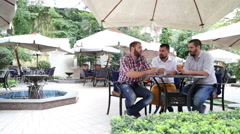 Men with beards sitting in cafe, drinking beer and communicating - stock footage