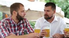 Three men with beards drinking light beer, talking and laughing - stock footage
