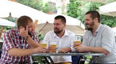 Three men with beards sitting in cafe, drinking beer and talking - stock footage