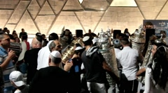Men dance with Bible scrolls during the ceremony of Simhath Torah - stock footage