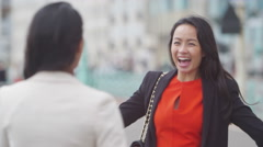 4K Attractive female friends meet up and greet each other outdoors in the city - stock footage