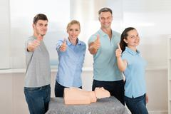 Group Of People Showing Thumbs Up Sign While Learning Resuscitation Training Kuvituskuvat