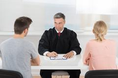 Mature Male Judge Sitting In Front Of Young Couple In Courtroom Kuvituskuvat