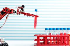 robot manipulates test tubes with dangerous chemicals - stock photo