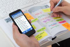 Close-up Of Person Hands Checking List From Mobile Phone And Diary Stock Photos