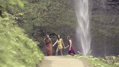 Young Women Hold Hands Walk Along Path Barefoot, Waterfall In Background Stock Footage