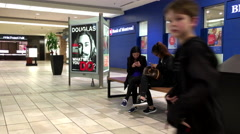 Close up people sitting at rest area and using new iphone 6s inside shopping Stock Footage