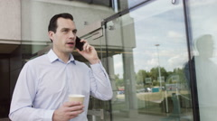 4K Attractive casual businessman talking on mobile phone outside office building Stock Footage